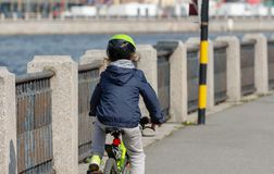 Little girl riding a bike in helmet. Little girl in a helmet rides a bicycle along the city embankment. view from the back. close-up royalty free stock image