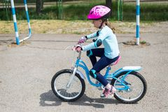 Little girl riding bike in outdoor, the free space. Stock Image