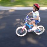 Little Girl Riding a Bike Speedy Fast Royalty Free Stock Image