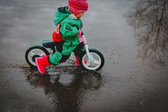 Little girl riding bike in spring water puddle. Seasonal activities for kids stock photos