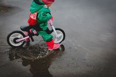 Little girl riding bike in spring water puddle. Seasonal activities for kids royalty free stock photos