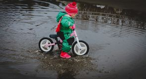 Little girl riding bike in spring water puddle. Seasonal activities for kids royalty free stock images