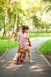 Little girl riding a bike on a sunny day Stock Photo