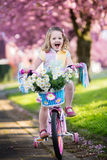 Little girl riding a bike on sunny spring day Stock Photo