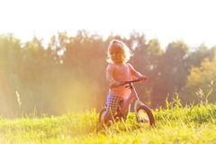 Little girl riding bike at sunset, active kids Royalty Free Stock Images