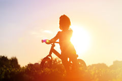 Little girl riding bike at sunset Stock Image