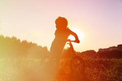 Little girl riding bike at sunset, active kids Royalty Free Stock Image