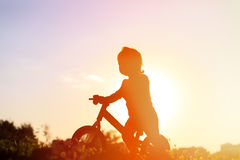 Little girl riding bike at sunset, active kids Stock Image