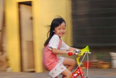 Little girl riding bycicle. Happy time in the evening royalty free stock photos