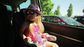 Little girl looks through the open window car. A little girl is riding a car with a hat and sunglasses stock video