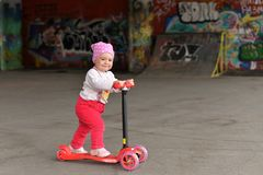 A little girl riding a children`s scooter in a skate Park stock photo