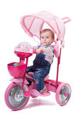 Little girl riding a children trike. Stock Images