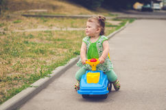 Little girl is riding a children& x27;s car Royalty Free Stock Photography