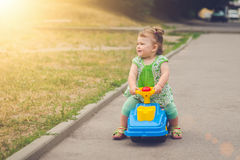 Little girl riding a children& x27;s car in the sunlight Stock Photos
