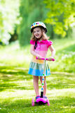 Little girl riding a colorful scooter Stock Images