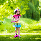 Little girl riding a colorful scooter Stock Photography