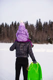 Little girl riding on dad outdoors in cold winter Royalty Free Stock Photos