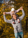 Little girl riding on dads neck at autumn park Royalty Free Stock Photo