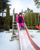 Little girl riding down the slide on playground at snowy day Royalty Free Stock Images