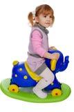 Little girl riding elephant toy. Studio shot Stock Photo