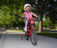 Little Girl Riding Fast on a Bike Stock Photo