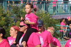 Little girl riding on fathers shoulders breast cancer walk Royalty Free Stock Photo