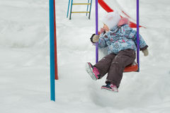 Little girl is riding on frosty winter playgrounds swing covering with white snow outdoors Stock Images