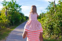 Little girl riding on her dad walking in the Stock Photo