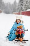 Little girl is riding her snow scooter with a toy Royalty Free Stock Images