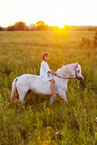 Little girl riding a horse. In a field Royalty Free Stock Images
