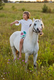 Little girl riding a horse. In a field Stock Photography