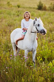 Little girl riding a horse. In a field Royalty Free Stock Image