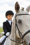 Little girl riding a horse participates in competitions. Summer countryside. Royalty Free Stock Images