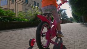 Little girl riding pink bicycle on bike path stock footage