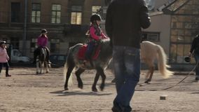 Little girl riding a pony in paddock stock footage