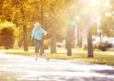 Little Girl Riding on Rollers and Enjoying Sunny Autumn Day stock image