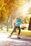 Little Girl Riding on Rollers and Enjoying Sunny Autumn Day stock images