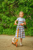 Little girl is riding a scooter Royalty Free Stock Photography
