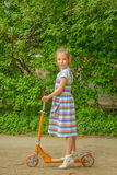 Little girl is riding a scooter Royalty Free Stock Images