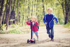 Little girl riding scooter and boy running, kids Royalty Free Stock Images