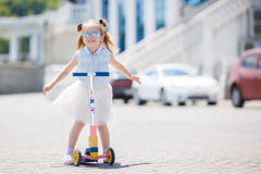 Little girl riding a scooter in the city Stock Images