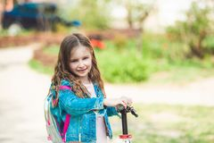 Little girl riding on scooter royalty free stock image