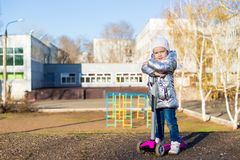 Little girl riding a scooter in the Park on a Sunny spring day. Active leisure and outdoor sport for children.  royalty free stock photos