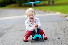 Little girl riding with scooter on the street Stock Photography