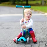 Little girl riding with scooter on the street Stock Images