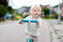 Little girl riding with scooter on the street Royalty Free Stock Photo