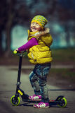 Little girl riding on a scooter Stock Photos