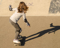 Little girl riding skateboard. With knee and elbow protection. Long sunset shadow Royalty Free Stock Photos