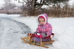 The little girl is riding on the sled in winter snow forest stock photo