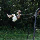 Little girl riding on a swing in the park Royalty Free Stock Photography
